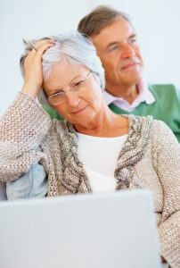 confused elderly couple looking at laptop